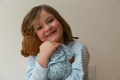 Little girl in striped shirt with messy dirty blonde hair hugging her teddy bear stock photo