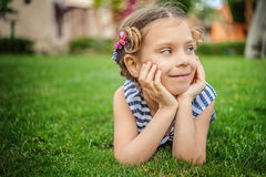Little girl in striped vest lies on green lawn Stock Image