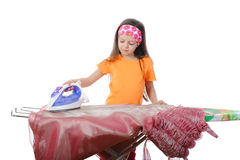 Little girl stroked her dress iron. Isolated on white background Royalty Free Stock Photo