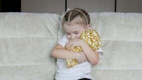 Little girl strokes and hugs a stuffed toy while sitting on the couch