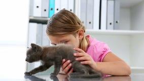 Little girl stroking a grey kitten