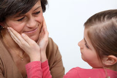 Little girl stroking mother's face Royalty Free Stock Photos