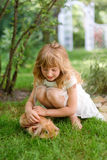 Little girl stroking a rabbit in the summer garden. Nature love and vegan concept. Little girl stroking a rabbit in the summer garden. Nature love and vegan Stock Images