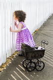 Little girl with stroller looking through fence Royalty Free Stock Photos