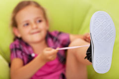 Little girl struggling to tie her shoes Royalty Free Stock Image