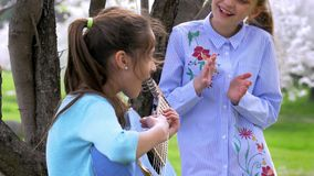 Little girl strums on guitar while her girlfriend standing clapping his hands listening music. wonderful spring day into. Little girl strums on a guitar while stock video footage