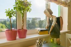 Little girl student with backpack in school uniform looks out the window, background is children`s room, desk, computer. School,. Education, knowledge and stock photos