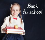 Little girl student in school uniform smiling. And holding pile of books ans apple on blackboard background with back to school handwriting stock photo