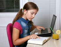 Little girl studies with a book and a laptop Royalty Free Stock Images