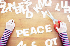 Little girl studies to write the word PEACE royalty free stock photos