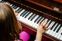 Little girl studing to play the piano Stock Photos