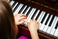 Little girl studing to play the piano Stock Photography
