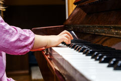 Little girl studing to play the piano Stock Photo
