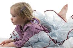 A little girl in studio. A little girl lying on the floor in studio Royalty Free Stock Image