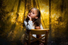 Little girl in studio setting. Young girl sitting in a studio chair with a gold background. She is posing to the camera stock images