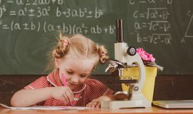 Little girl study in chemistry classroom at school. Schoolgirl work on chemistry research with microscope, vintage. Filter royalty free stock photo