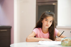 Little girl studying. Looking at cameta Stock Image