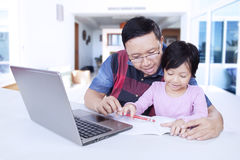 Little girl studying with dad on the table at home Stock Image
