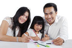 Little girl studying with her parents Royalty Free Stock Images