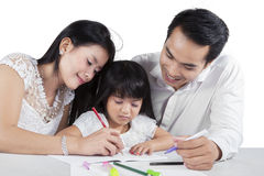 Little girl studying with her parents Stock Image