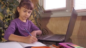 Little girl studying on a laptop stock footage