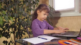 Little girl studying on a laptop stock video