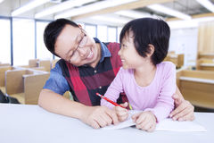 Little girl studying with male teacher in class Royalty Free Stock Photo