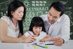 Little girl studying with parents at class Stock Photos