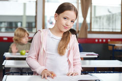 Little Girl Studying While Standing At Desk stock photography