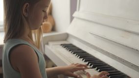 Little girl studying to play the piano at home. Preschool child having fun with learning to play music instrument. Education, skills concept stock video