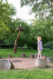 Little girl on stump in the park Royalty Free Stock Photography
