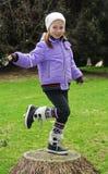 Little girl on stump Stock Images