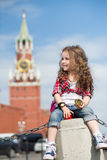 The little girl in stylish dress near the Kremlin sitting. On concrete with a compass in hand royalty free stock photography