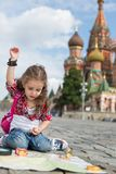 The little girl in stylish dress with raised hand up sitting. Near the Saint Basils Cathedral on the sett with map, magnifier and compass royalty free stock image