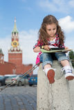 Little girl in stylish dress sitting on concrete. The cute little girl in stylish dress sitting on concrete near the Kremlin and looking on the map with royalty free stock image
