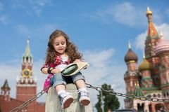 The little girl in stylish dress sitting on concrete near the Kremlin. With a map and magnifier in hand stock images