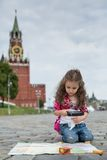 The little girl in stylish dress sitting near the Kremlin Stock Photos