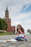 The little girl in stylish dress sitting near the Kremlin. On the sett with map and looking through a magnifying glass stock image