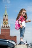 The little girl in stylish dress and sunglasses near the Kremlin. With a compass in hand stands on concrete block royalty free stock image
