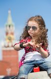 The little girl in stylish dress and sunglasses near the Kremlin. Sitting on concrete with a compass in hand and toy box with the inscription Russia stock photography