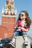 Little girl in stylish dress and sunglasses near the Kremlin. Sitting on concrete with a toy music box stock image