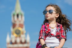 Little girl in stylish dress and sunglasses sitting. Near the Kremlin stock photos