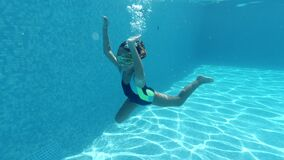 Little girl submerged in blue transparent water of swimming pool