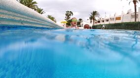 Little girl submerged in water swimming in pool