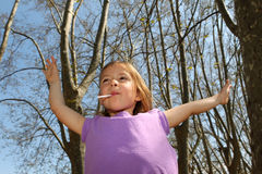 Little girl sucking lollipop. And raising arms in the air by some trees Stock Photo