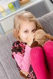 Little girl sucking thumb hugging toy dog. Little girl sitting on sofa at home, sucking thumb, hugging soft toy, smiling Royalty Free Stock Photo