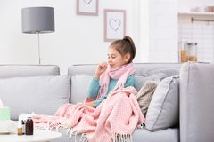 Little girl suffering from cough and cold on sofa royalty free stock images