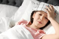 Little girl suffering from headache while lying in bed. At home Royalty Free Stock Photo