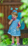 The little girl in a suit of the fairy longs with  scarlet flore Royalty Free Stock Photos
