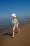 The little girl suit goes on water. The little girl in a bathing suit goes on water Stock Image